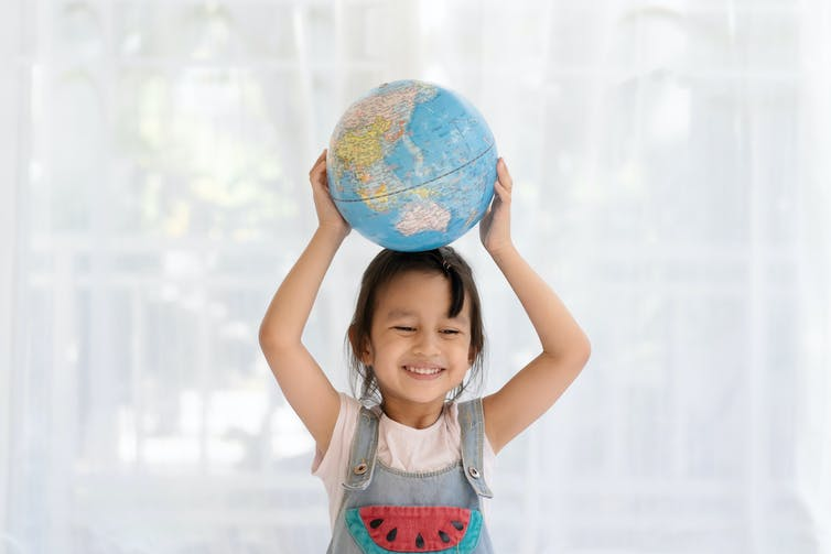 A young girl holding a globe on her head