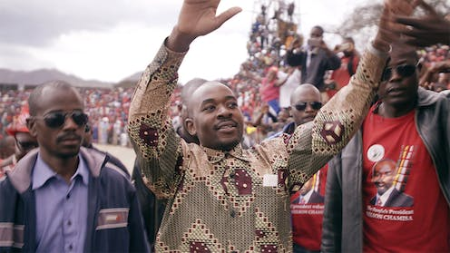 three men in front of a huge crowd. The man in the centre holds his hands up with a small smile. He is shaven headed and wears an African print shirt.