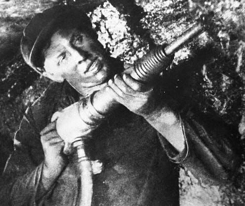 Man drilling in coal mine.
