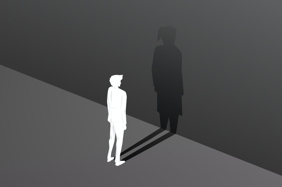 Silhouette of male and his bigger shadow as a female against a wall.