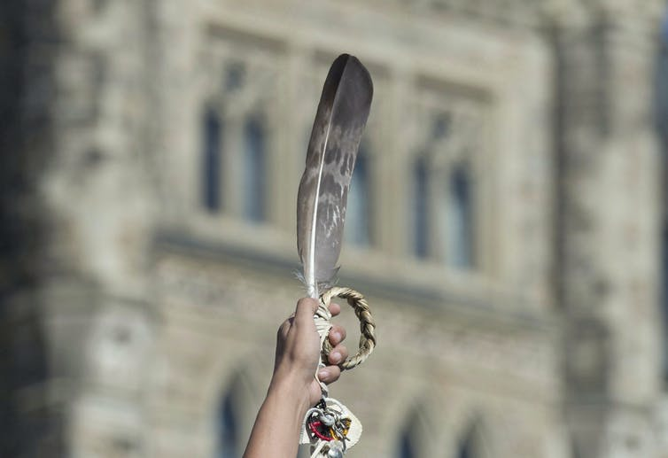 Woman holds up an eagle feather and sweetgrass braid in front of a bricked building that is blurred in the background.