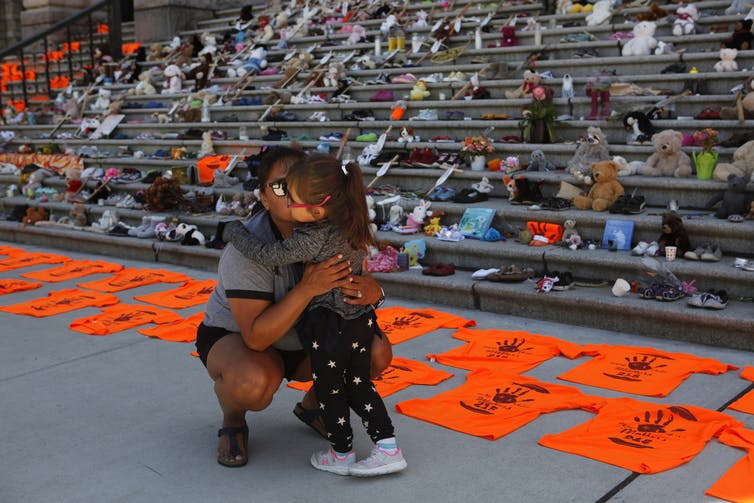 Woman and daughter hug in front of steps covered in shoes and orange t-shirts