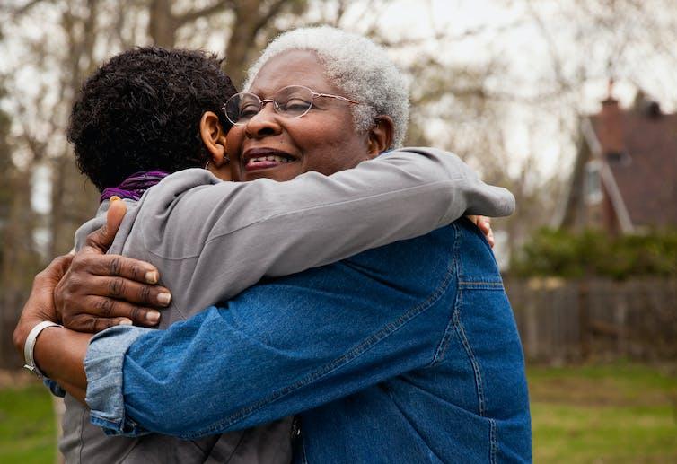 A older women hugs her daughter.