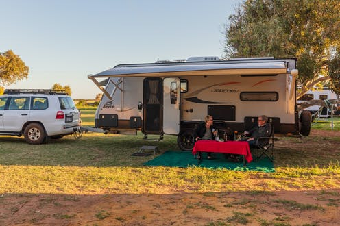 Couple sitting at table next to caravan in park