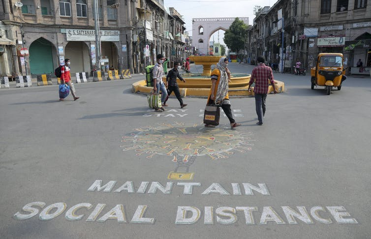 A sign advises locals to 'maintain social distance' in a Hyderabad street.