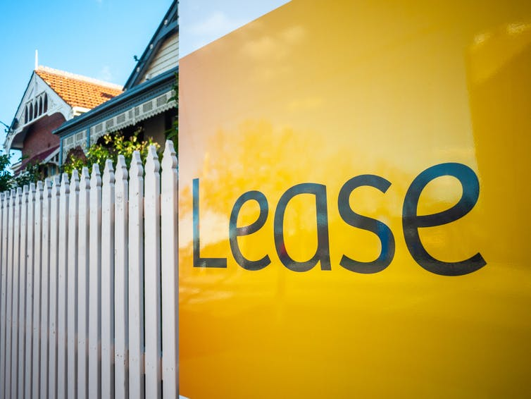 Lease sign on front fence of house