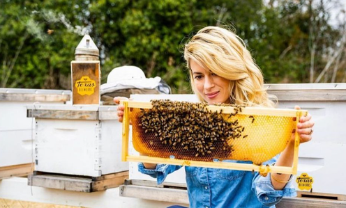 """Texas Beeworks's Erika Thompson (AKA the """"TikTok bee lady"""") holds up a honeycomb covered in bees, with no protective equipment, bare hands and free-flowing hair."""