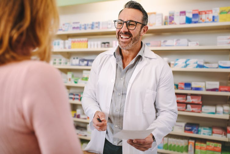 A male pharmacist talks with a female customer.