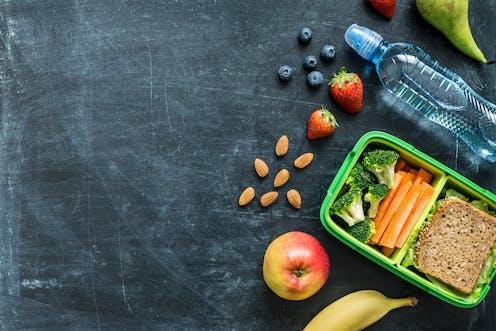 A healthy lunch is unpacked on a blackboard.