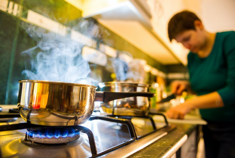 woman cooks in kitchen with gas stove
