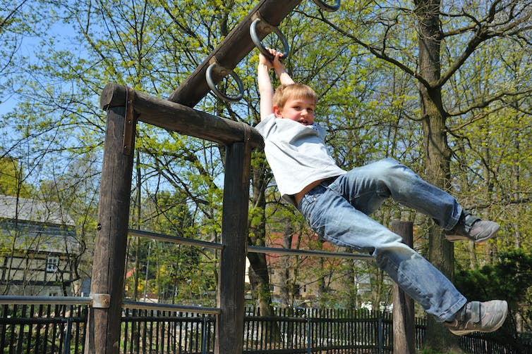 Child swings from monkey bars at a playground.