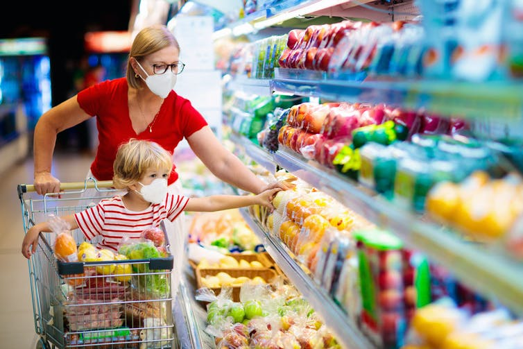 Mother and child shop for vegetables at the supermarket.