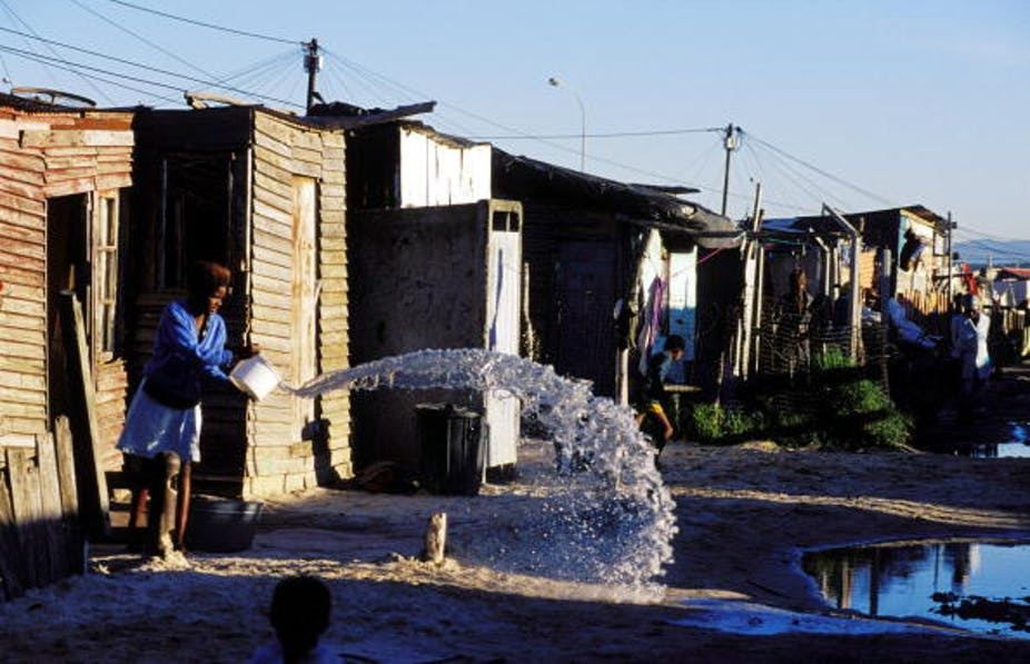 A girl throws out water from a bucket into the street in a shackland in Khayelitsha, a poor black township in Cape Town.