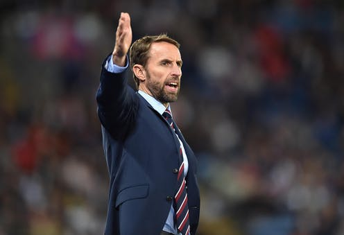 England manager Gareth Southgate wearing a blue suit and striped tie on a football pitch