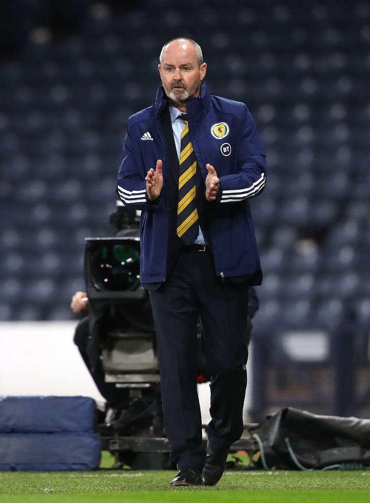 Scotland team manager Steve Clarke wearing a striped navy and yellow tie and a blue jacket on a football pitch