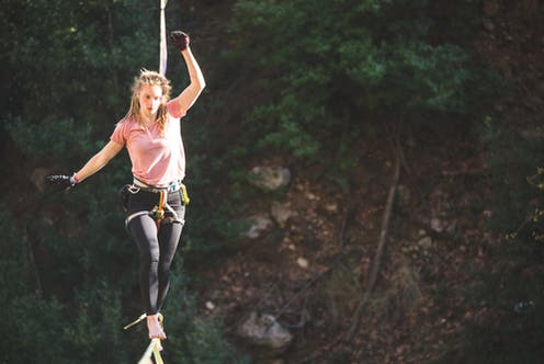 Woman on balancing on a tightrope with a harness