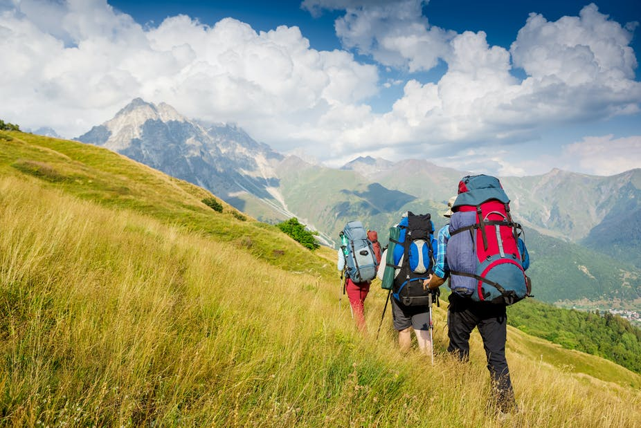 A group of three hikers with large backpacks climbs up a grassy hill.