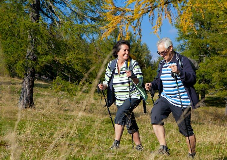 An older couple use trekking sticks while hiking.