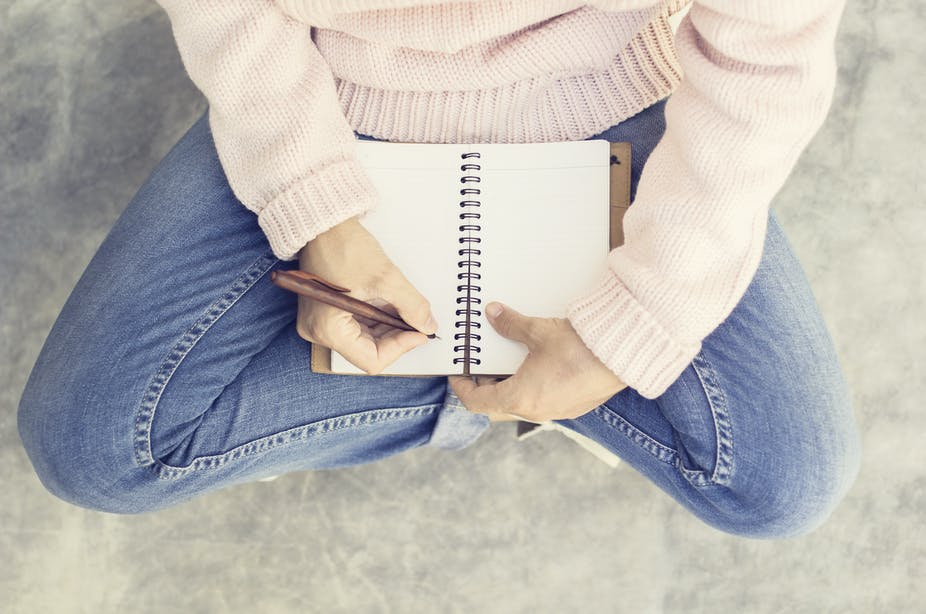 Girl wearing a cream jumper and blue jeans seen from the arms down sitting cross=legged on a concrete floor and writing in a notebook.