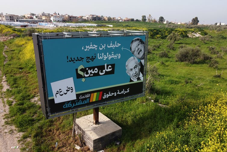 A campaign billboard for Arab parties in Arabic with pictures of Israeli Prime Minister Benjamin Netanyahu and Israeli far-right leader Itamar Ben Gvir.
