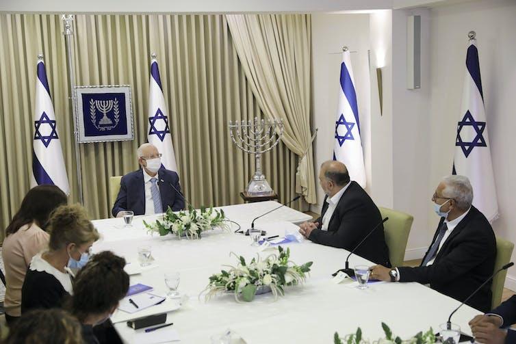 Un grupo de personas se sienta en una mesa grande con mantel blanco y banderas israelíes al fondo.