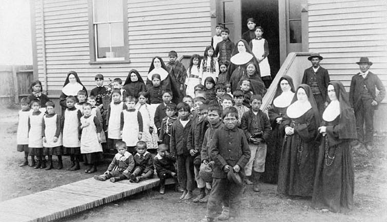 A group of nuns with Indigenous children stand outside of a building, black and white photo