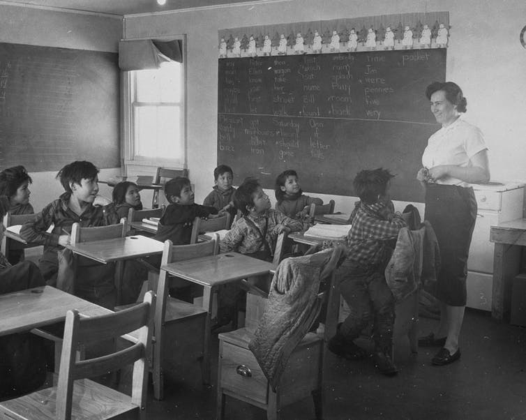 Indigenous students sit at desks in a classroom looking up at a teacher