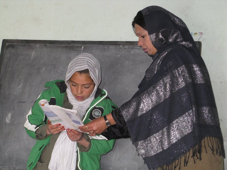 In front of a black board, a female teacher stands beside a girl and helps her hold a book, while the girl is reading.
