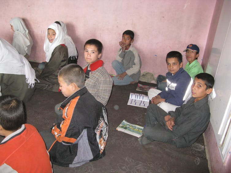 Boys sit on the ground in a school.