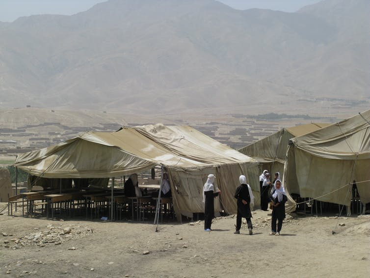Female students inside a tent.