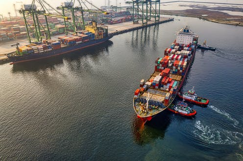 Tug boats push a large cargo ship in port.