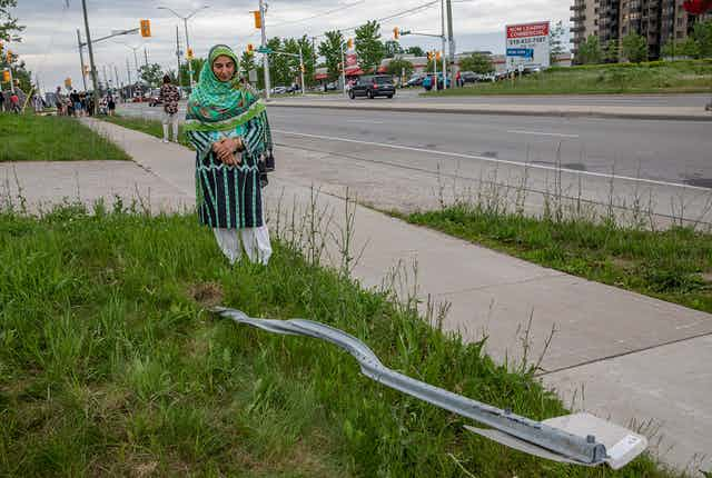 A woman wearing a hijab stands next to a destroyed street sign.