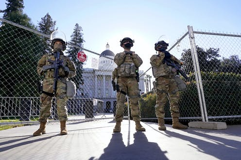 Armed soldiers stand near a fence outside the California Capitol building