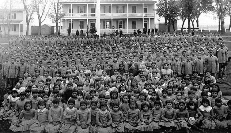Archive photo of hundreds of Native American children in a boarding school around 1900.