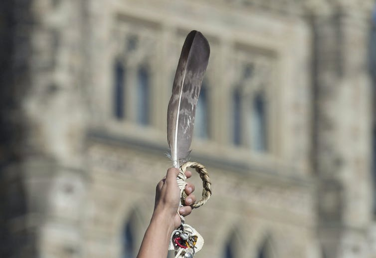 An eagle feather is held up during a rally.