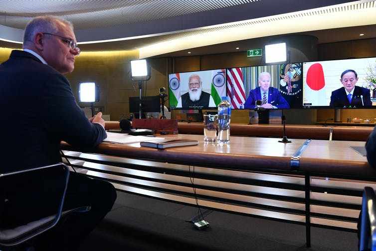 political leader in suit sits at desk in video conference with 3 others