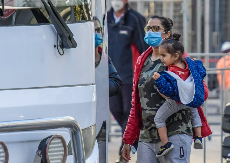 Women in mask carries a child on her hip as she boards a bus