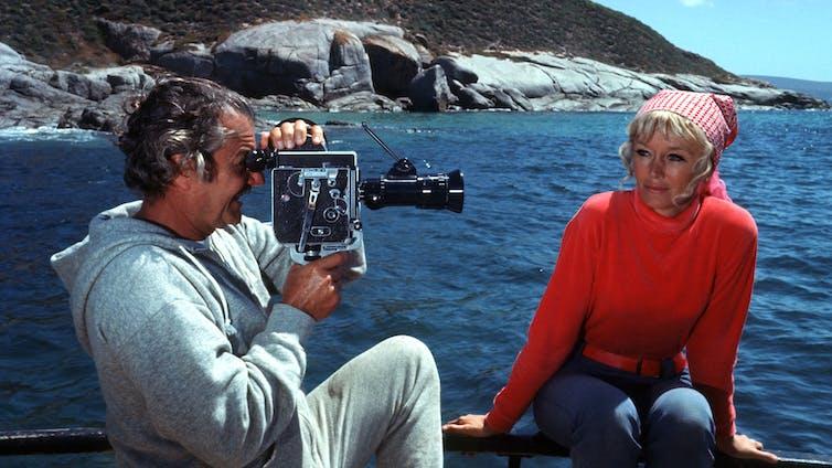 man films woman on boat