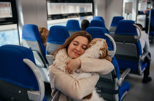 Young woman hugs her dog while travelling on a train
