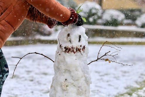 child builds snowman