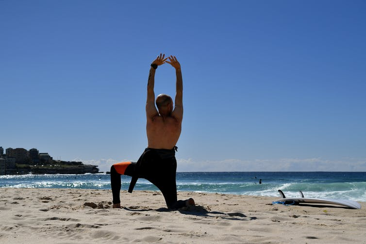 A man stretches on a beach.