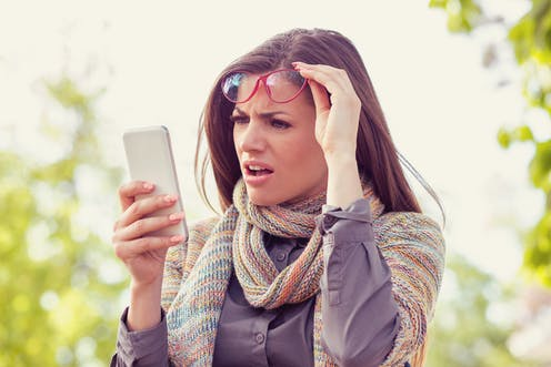 Woman looking at her phone with a surprised expression.