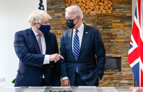 Boris Johnson and Joe Biden wearing face masks, observe the original Atlantic Charter. Johnson appears to be speaking to Biden.