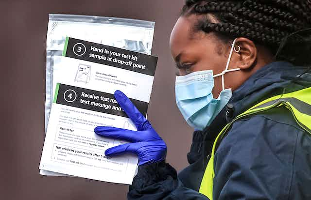 A woman hands out self-test kits at a COVID testing centre in Bolton, England.