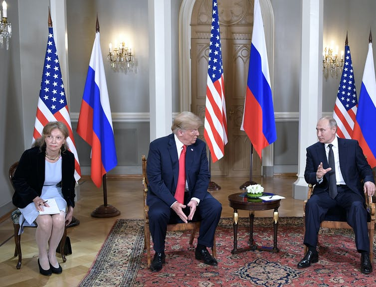 Donald Trump and Vladimir Putin sitting in chairs, in conversation. A US translator is sitting next to Trump, and American and Russian flags are in the background.