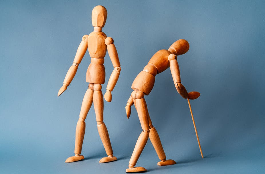 Two wooden artist figures representing a young healthy body and a stooped, ageing one with walking stick.