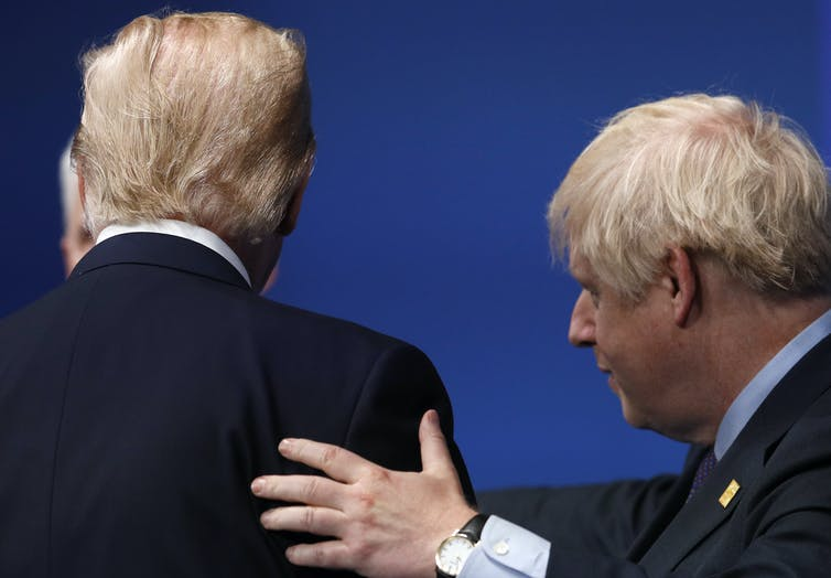 Boris Johnson places his hand on Donald Trump's back during a meeting between the two at a NATO summit. Trump is facing away from the camera.