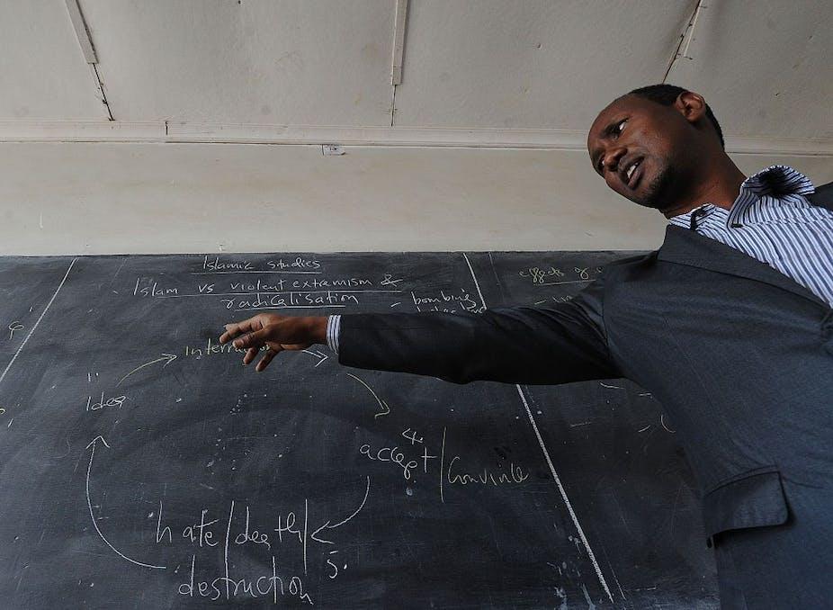 Kenyan teacher giving a lesson in front of a blackboard.