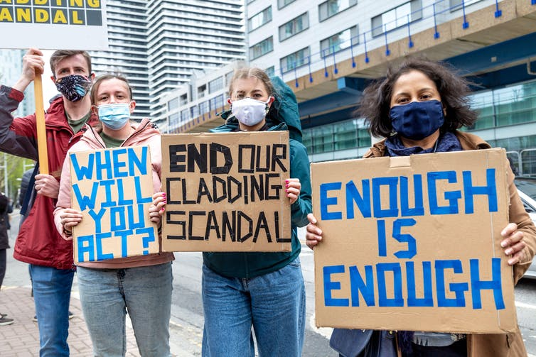 Protestors carry signs saying 'WHEN WILL YOU ACT?' 'END OUR CLADDING SCANDAL', and 'ENOUGH IS ENOUGH'.