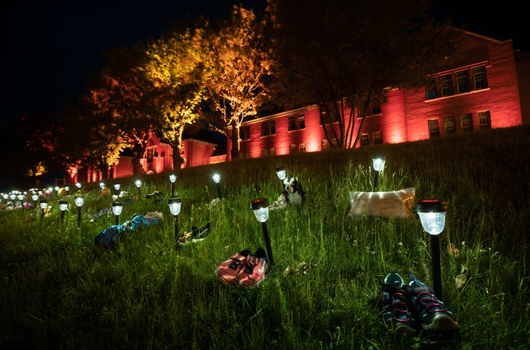 Shoes are placed on the lawn outside the former Kamloops Indian Residential School.
